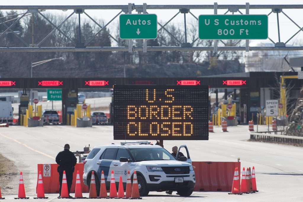 """An electronic sign reading """"US Border Closed"""" at the country's border with Canada."""
