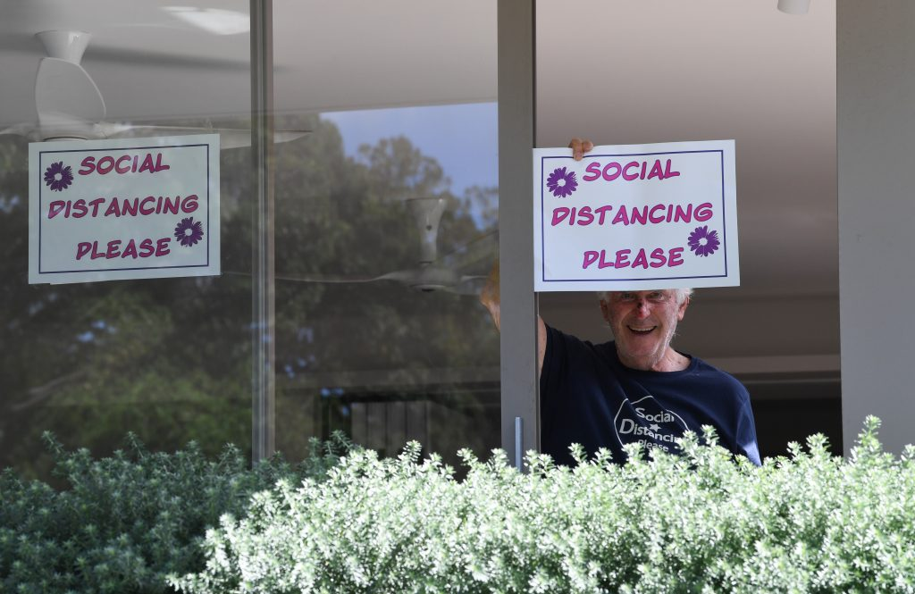 """A man inside a house holds up a hand-drawn sign that says """"Social Distancing Please."""""""