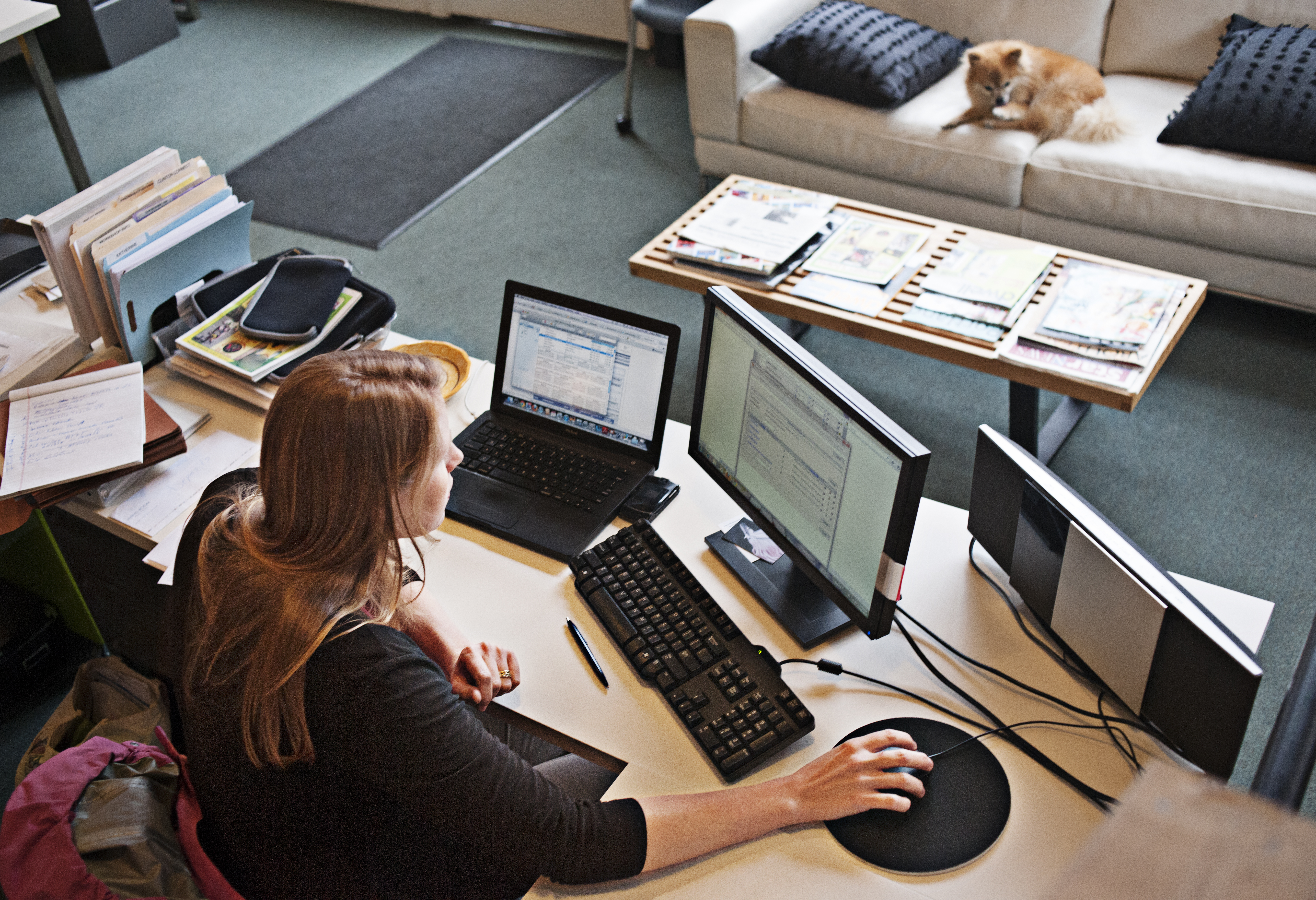 A woman works at an office desk that is located in a private living room.