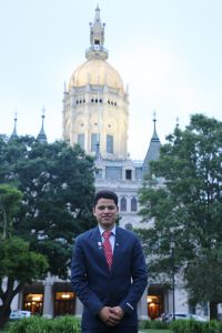 Michael Hernandez, UConn's fifth Newman Civic Fellow, poses in front of the state Capitol in Hartford.