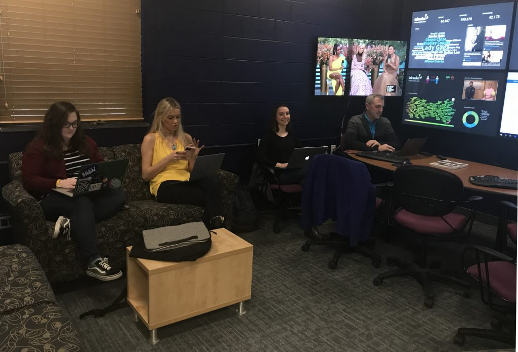Students and faculty members sit before the multi-screen bank of the Social Media Analytics Command Center at UConn.