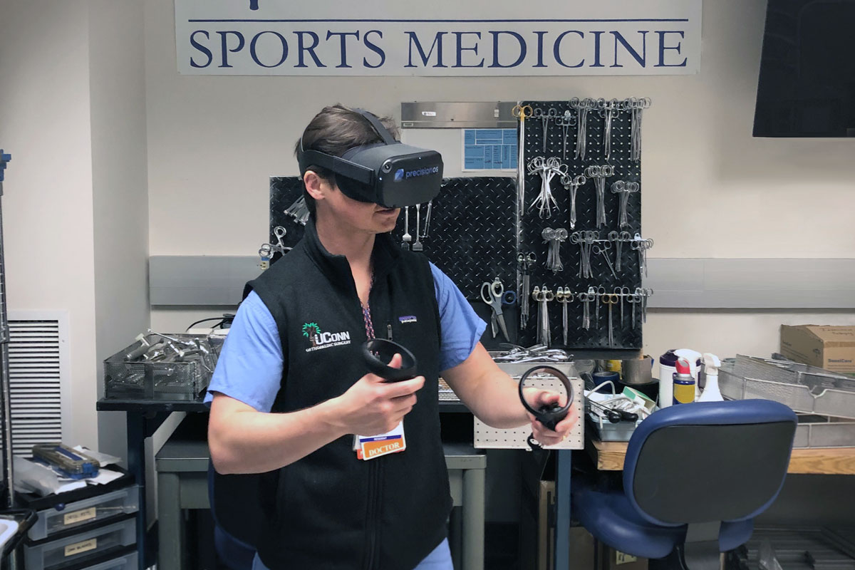 Dr. Merrill wearing virtual reality goggles and holding simulator controllers