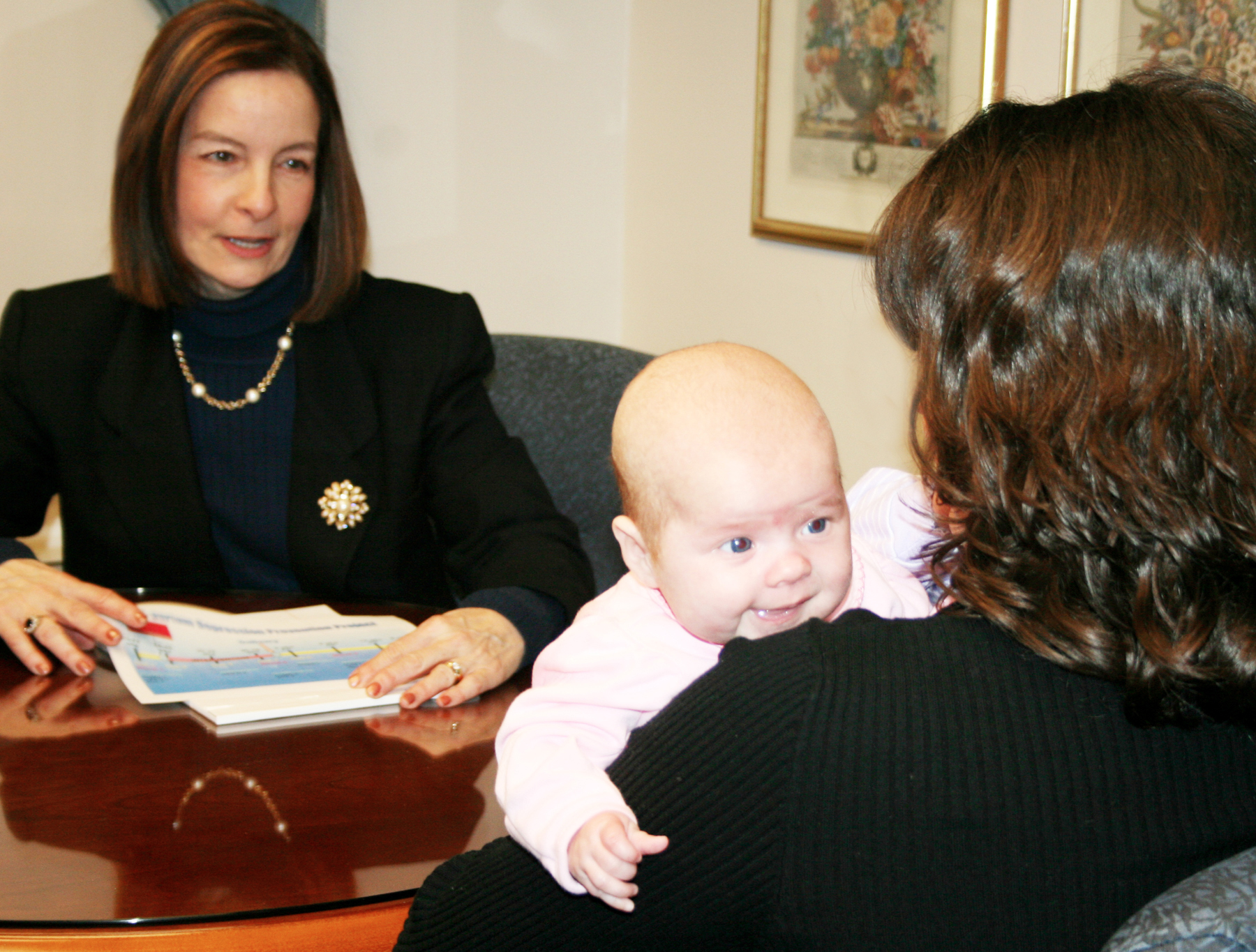 Professor Cheryl Beck meeting with a mother and infant child.