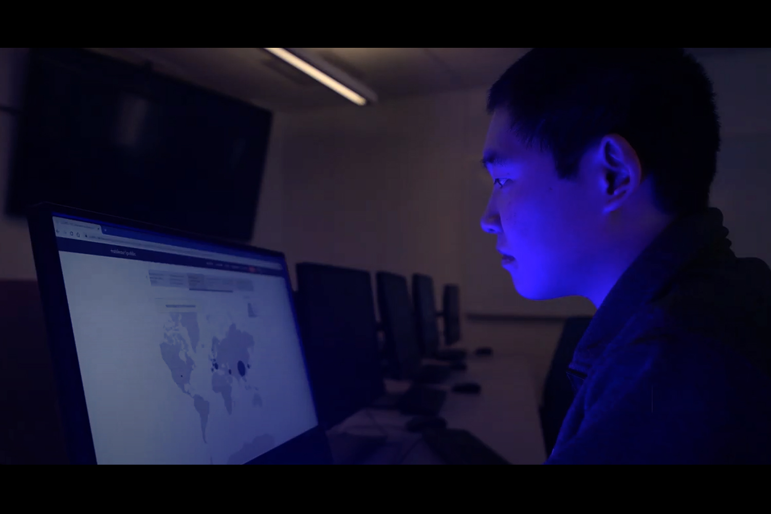 Yuansun (Sonny) Jiang looks at a laptop screen displaying a map of coronavirus cases worldwide in a dark room.