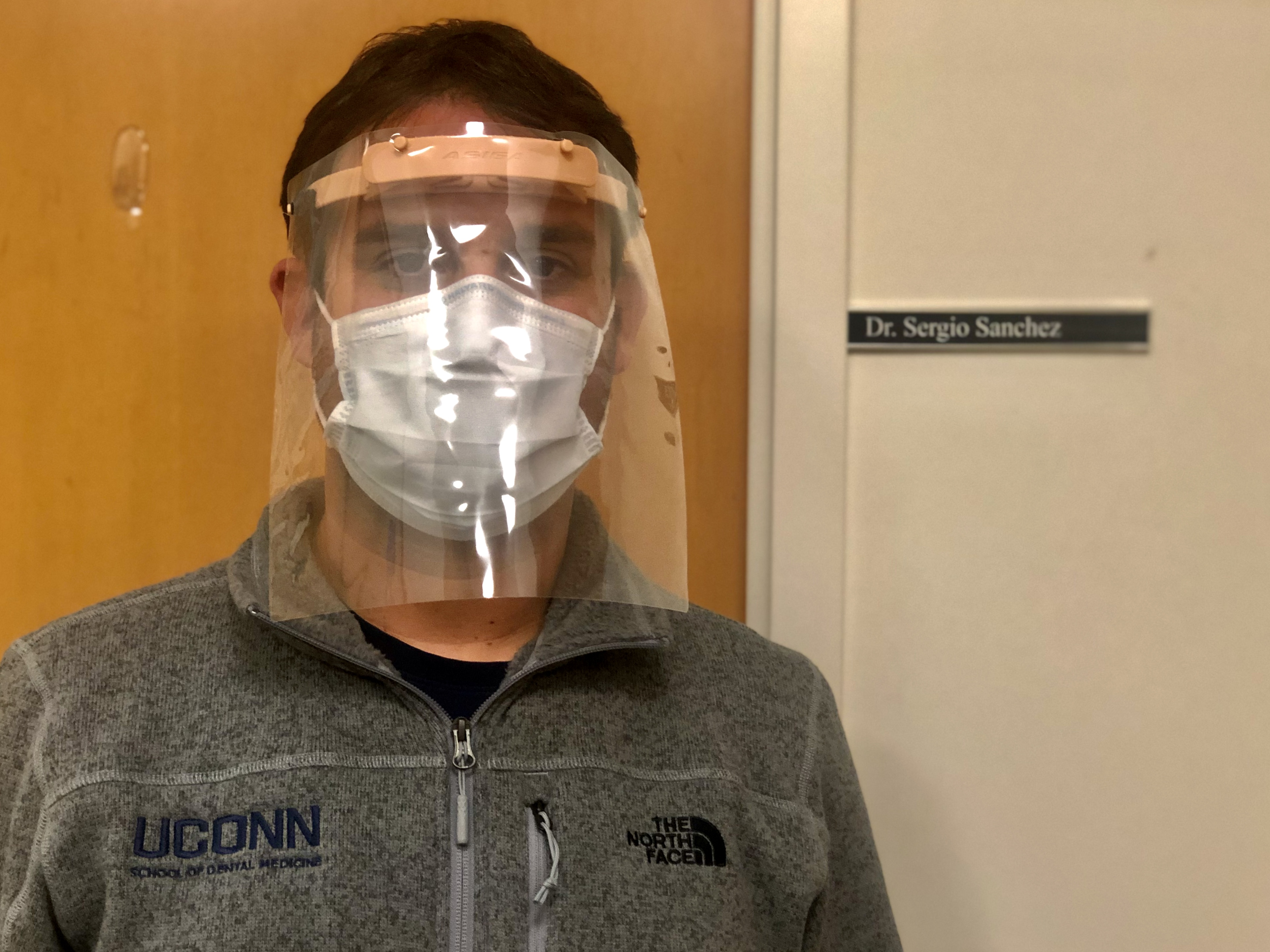 Dr. Sergio Sanchez Velasco models a face shield made through the 3D printing process to help protect dental residents and other health care workers from exposure to the novel coronavirus. (UConn Health Photo)