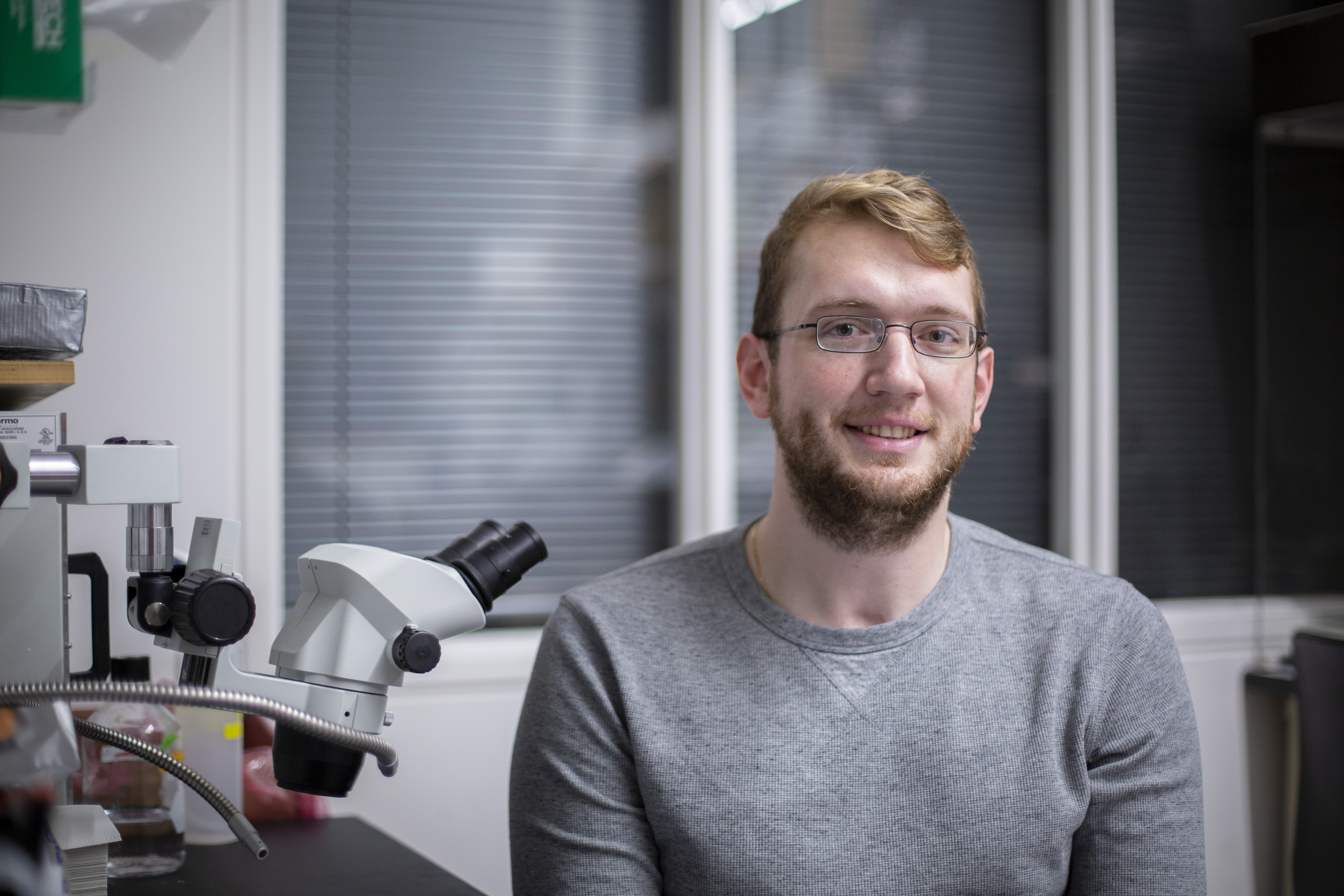 Jeff Rasumussen '20 (CLAS) sits by a microscope in his PNB lab.