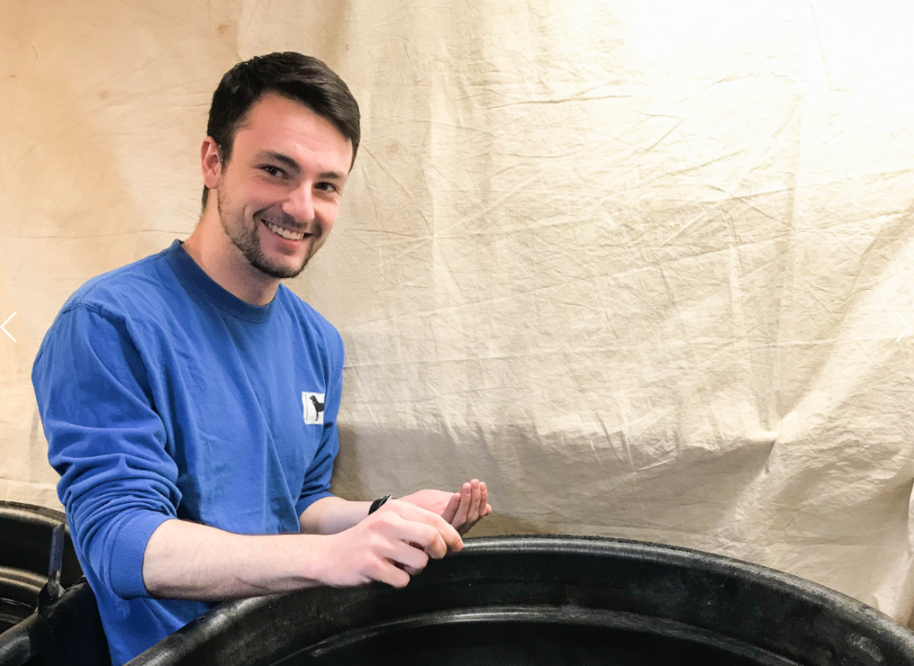Student entrepreneur Peter Goggins poses near some barrels containing fish whose feed he is experimenting with.