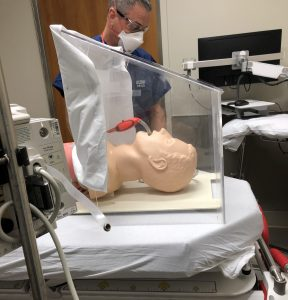 A health care worker looks at a mannequin head displayed inside an intubation hood designed by two UConn Health doctors.