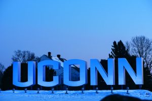 Blue lights casting across the large UConn branded sign at night during the winter on Jan. 22, 2020. (Sean Flynn/UConn Photo)