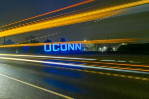 Large UConn sign lit up at night with light trails from car traffic.