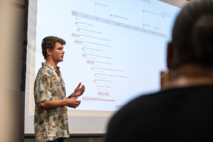 A student, Zac Will, wearing a Hawaiian shirt while making a presentation in front of a class.
