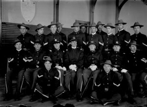 Military cadets pose for a photograph taken in 1904, probably in the auditorium in Old Main, which was the central campus builiding from 1890 to 1928. The plaque to the left above the cadets honors Nicholas Hawley, a fellow cadet who died of typhoid fever during the Spanish American War in 1898.