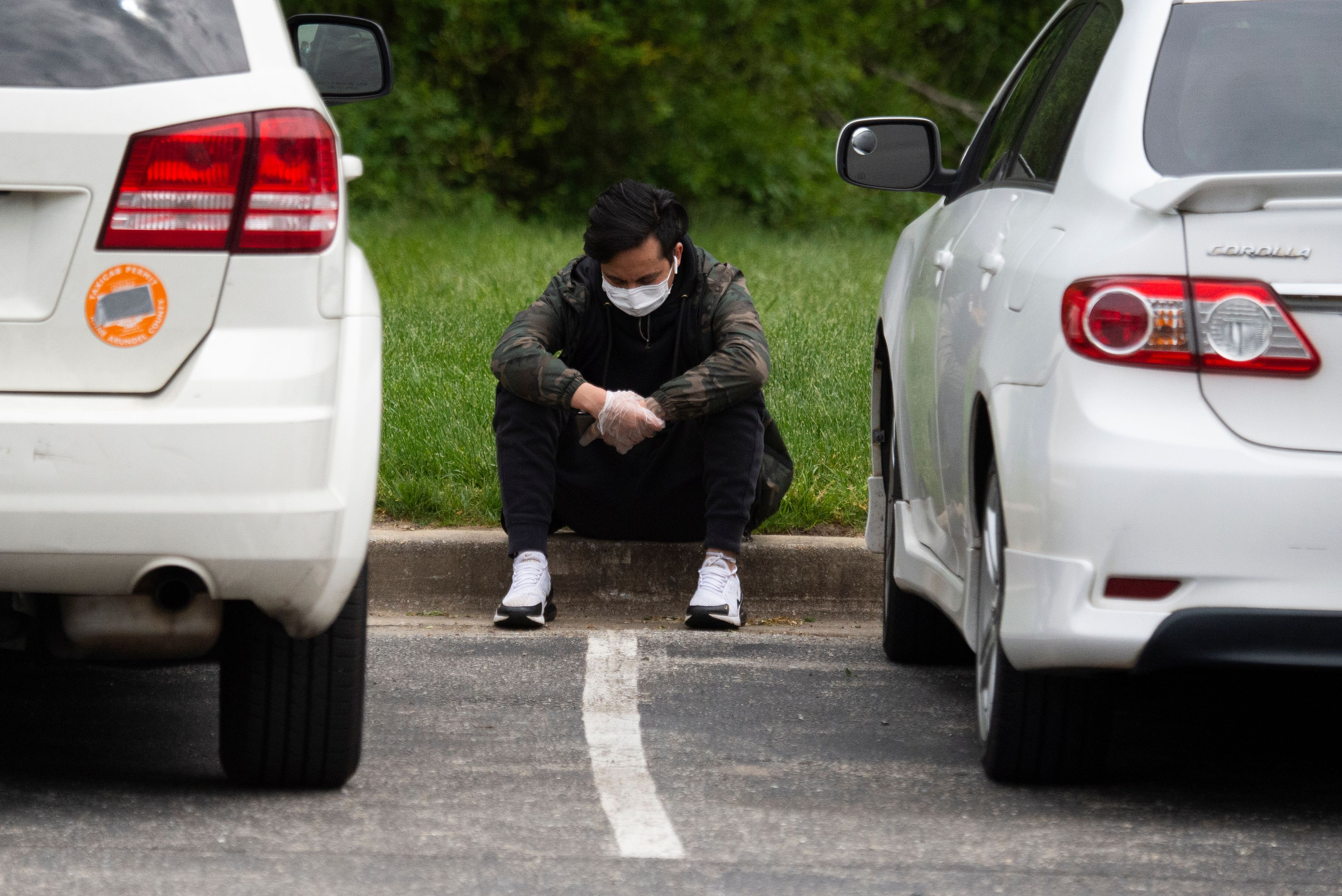 A mourner from the Nepali community, unable to attend the funeral for Ashish KC due to social distancing restrictions, reacts in the parking lot outside of the Maryland Cremation services in Millersville, Maryland on May 20, 2020. - Ashish died in a drowning but due to restrictions in place amid the novel coronavirus pandemic, only eight close family members and friends were allowed to attend the ceremony inside, while more then 30 waited outside. Mourners inside live streamed the funeral to family back in Nepal and to those waiting just outside. The coronavirus pandemic has drastically altered the way we are able to mourn and say goodbye to loved ones. (Photo by ANDREW CABALLERO-REYNOLDS / AFP) (Photo by ANDREW CABALLERO-REYNOLDS/AFP via Getty Images)