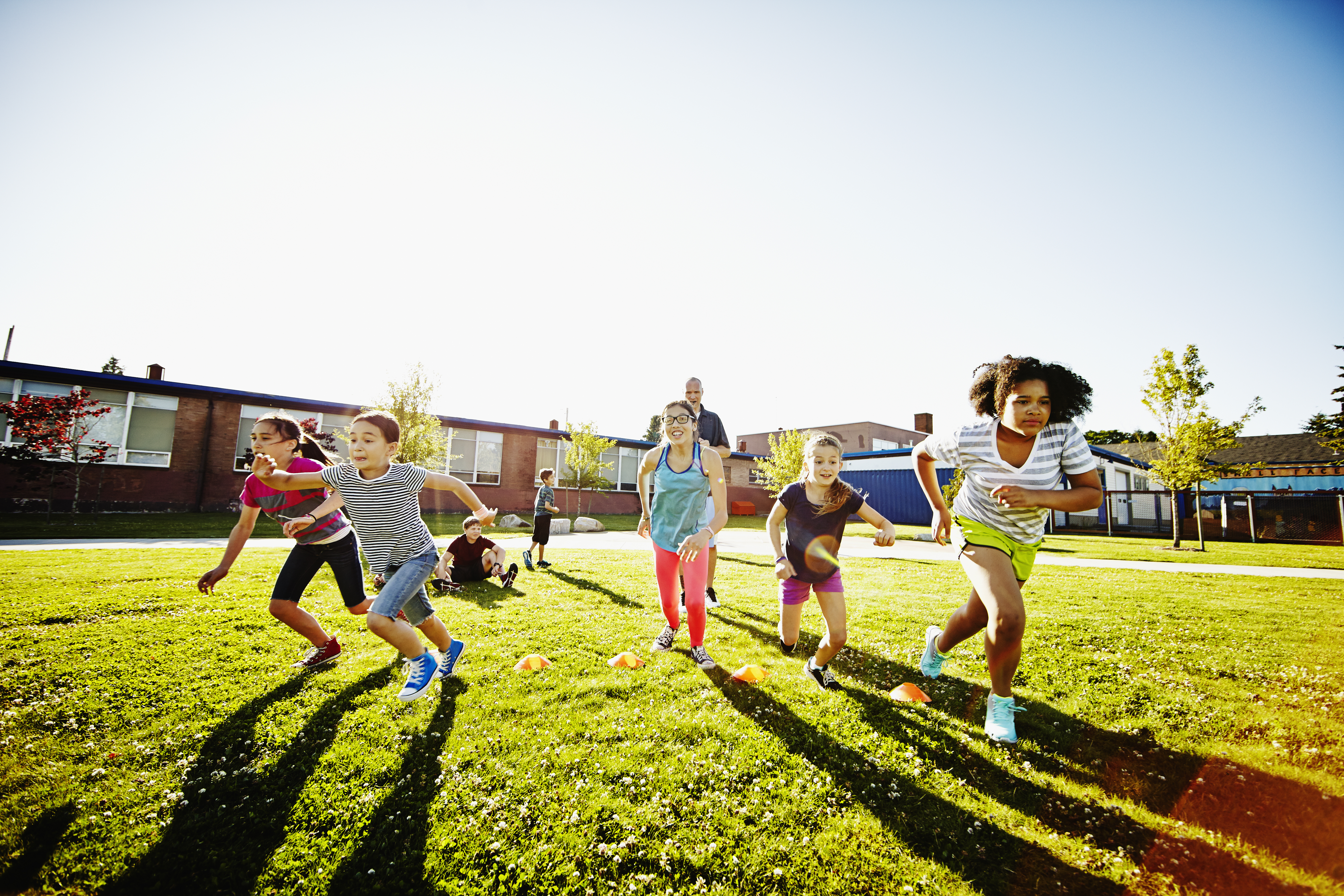 A group of elementary school girls have a foot race while a coach or teacher looks on.