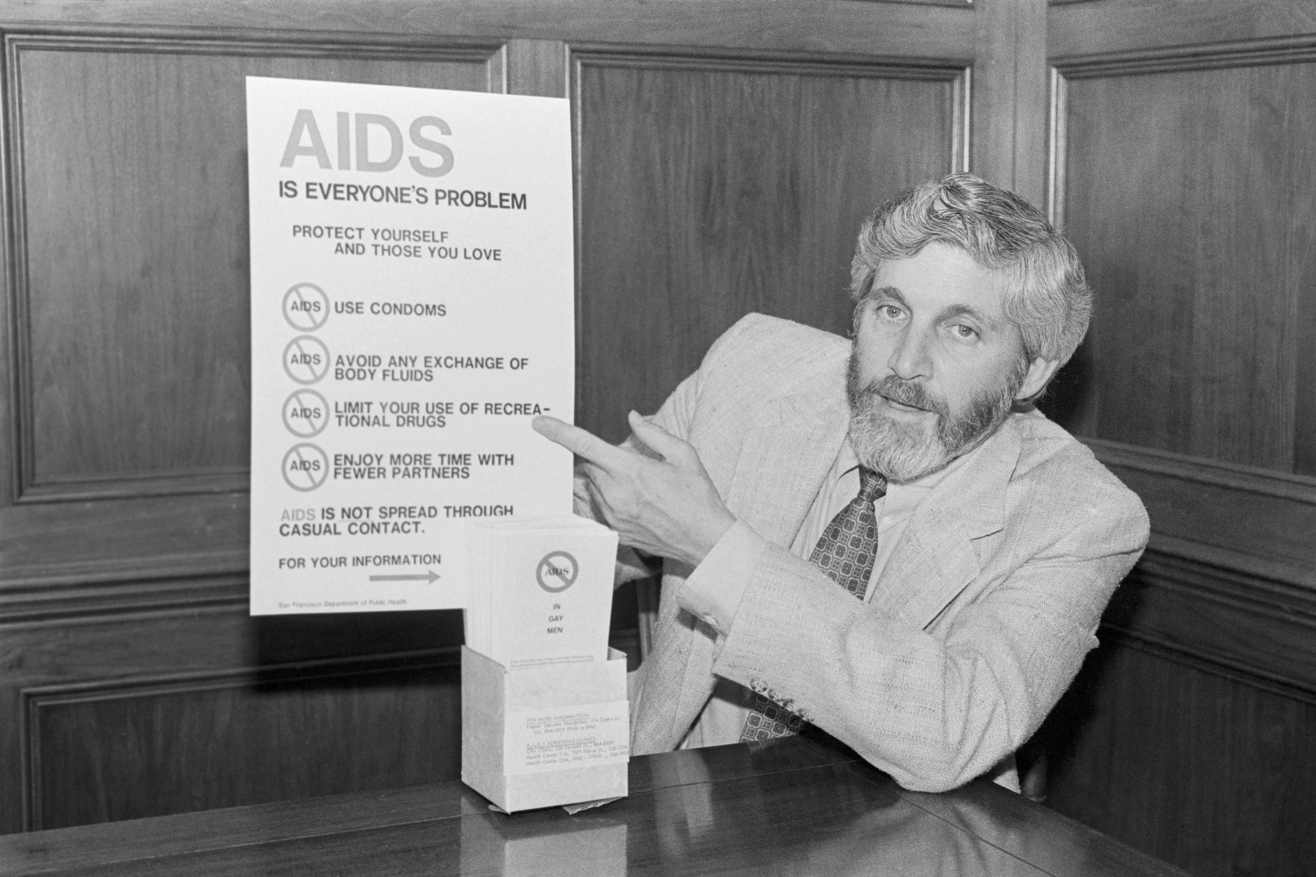 Dr. Mervyn F. Silverman, Director Of Health for the City and County of San Francisco, displays poster and leaflets during the early years of the HIV/AIDS epidemic.