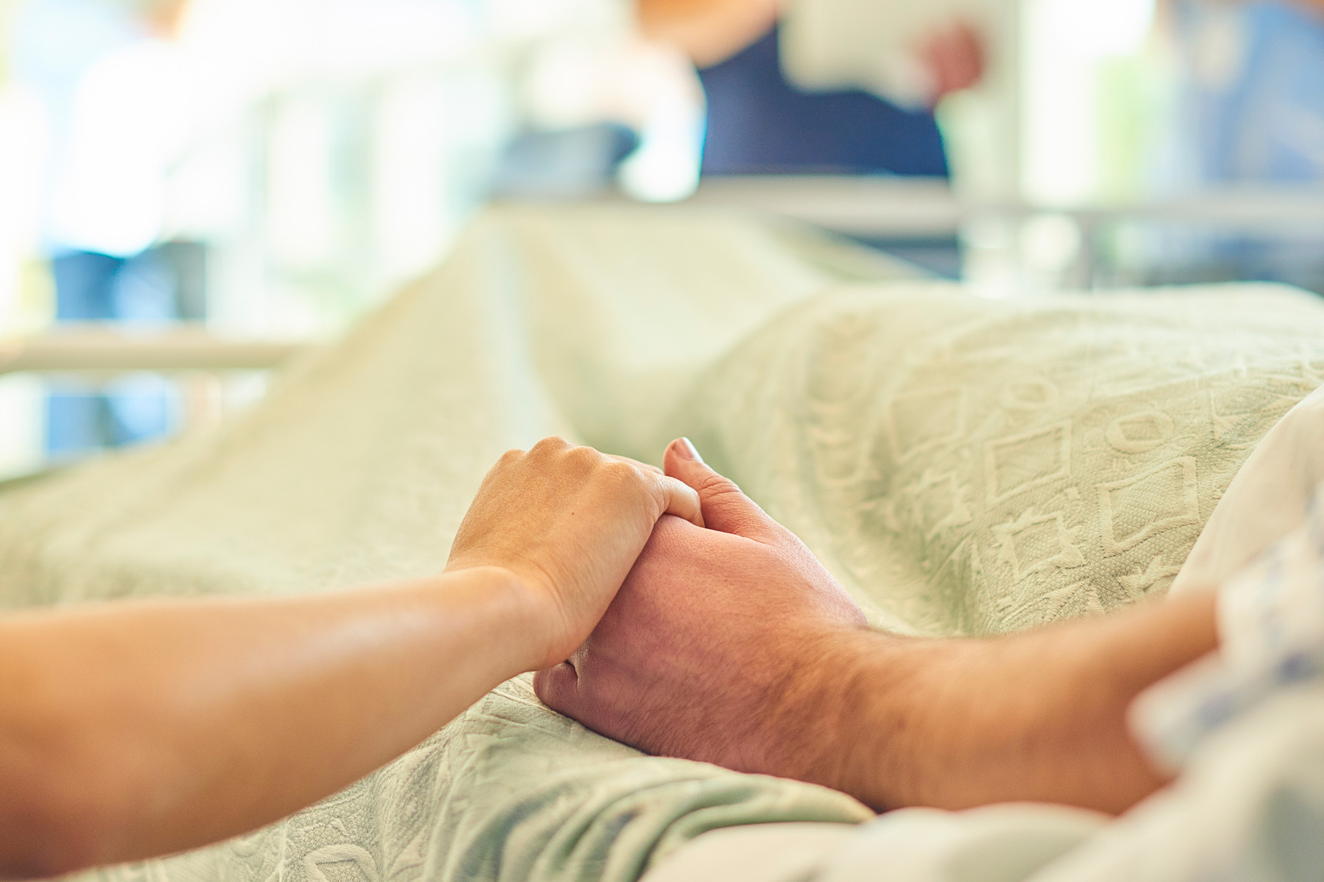 Two people holding hands in a hospital room.