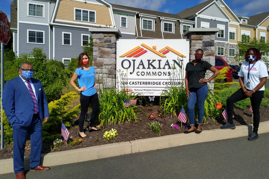 Group portrait (wearing masks) by the sign for Ojakian Commons