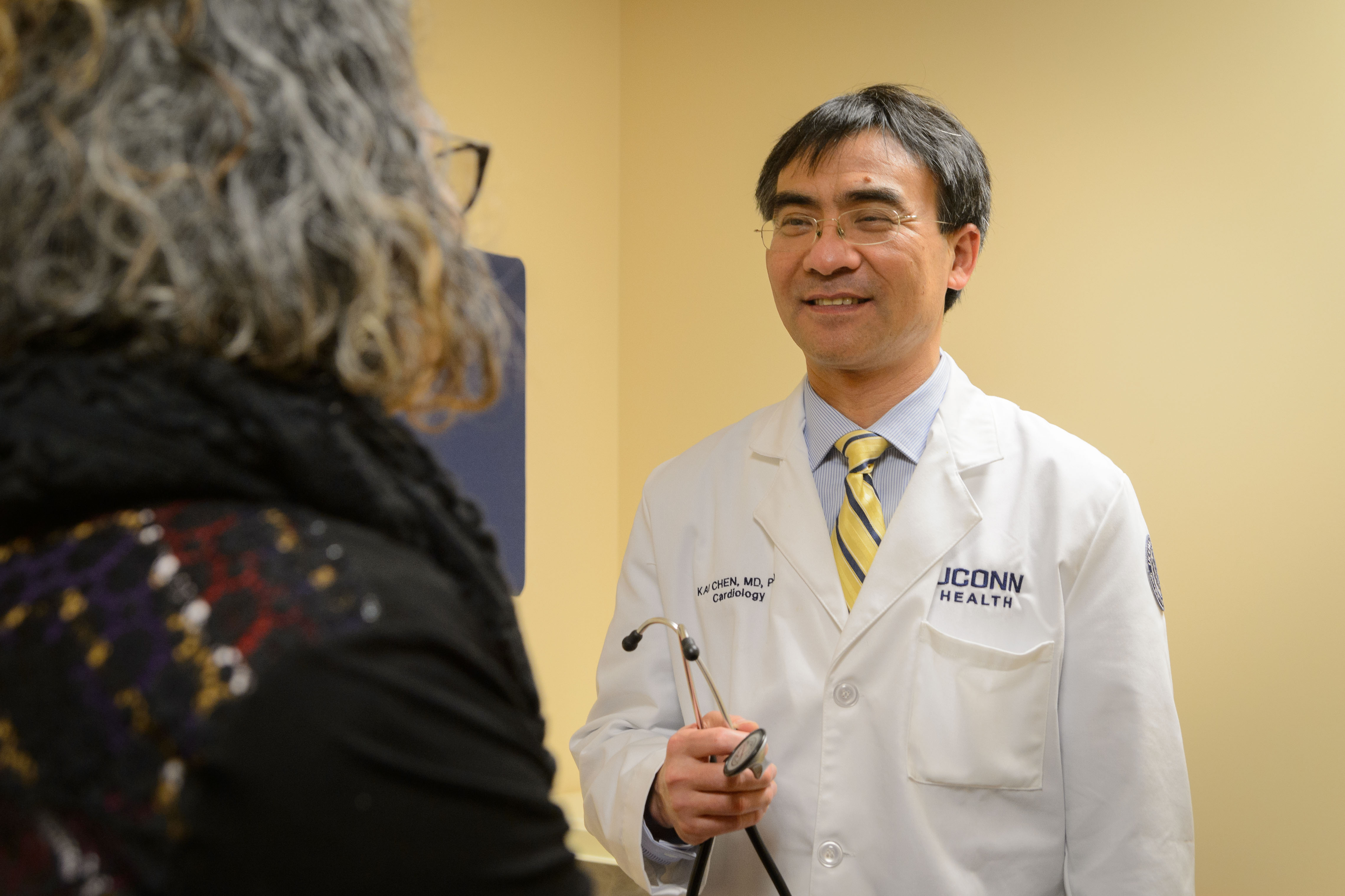 Dr. Kai Chen of UConn Health meets with a patient.