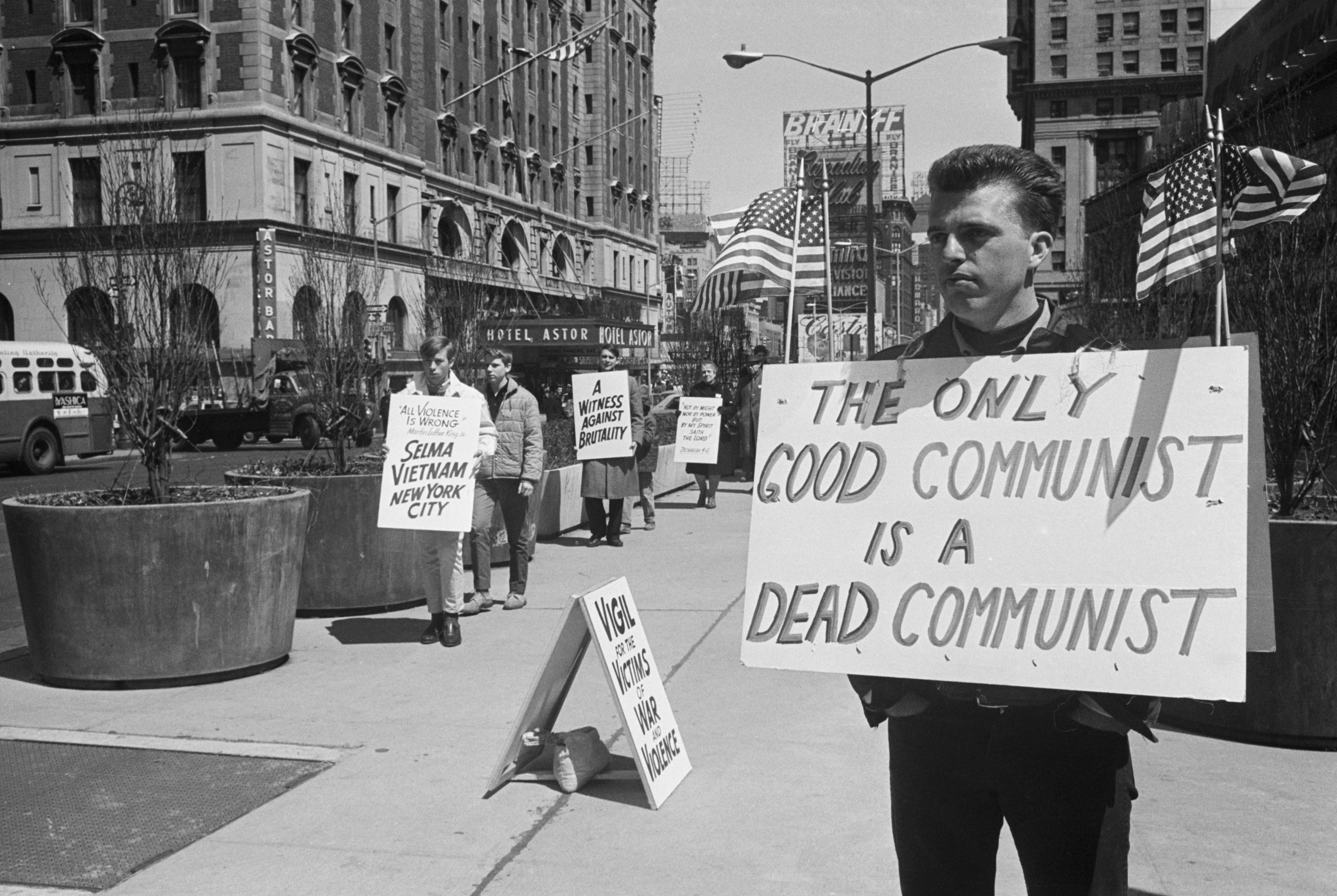 """Antiwar protesters in 1965 stand to the left of a counter-demonstrator with a sign reading """"The Only Good Communist is a Dead Communist."""""""