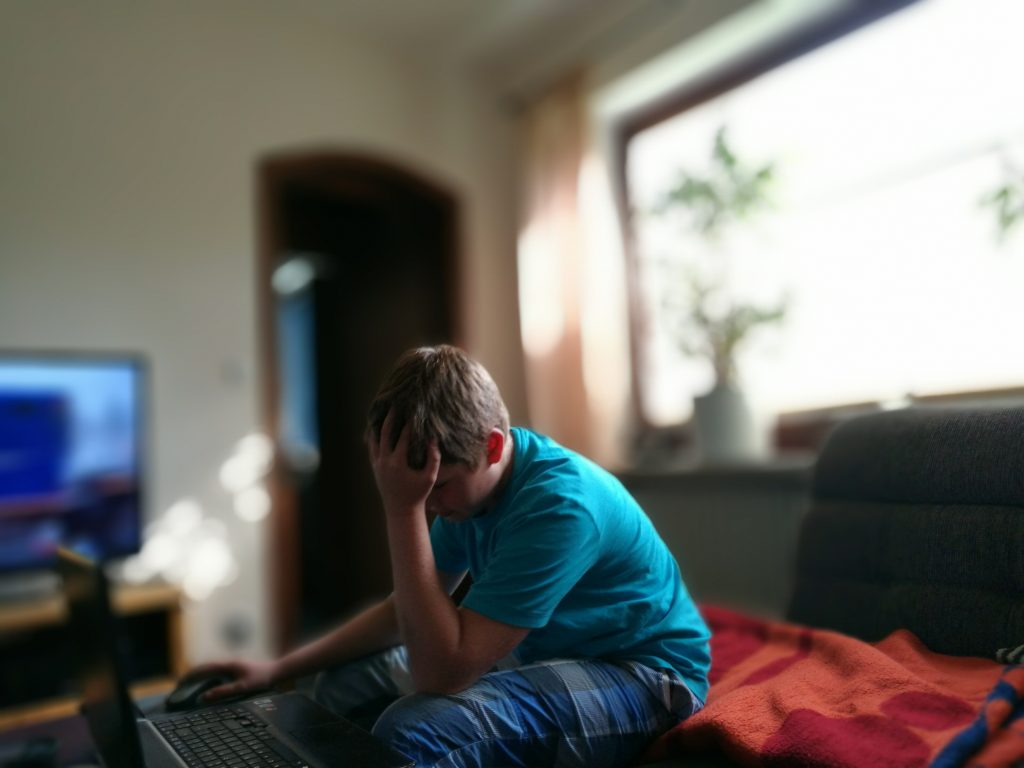 Frustrated Teenage Boy Using Laptop With Head In Hand At Home