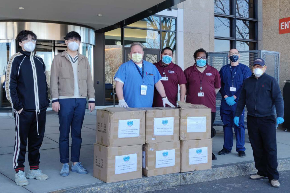 Representatives of groups that donated and UConn Health staff/vendors with six boxes of personal protective equipment in front of the UConn Health main entrance