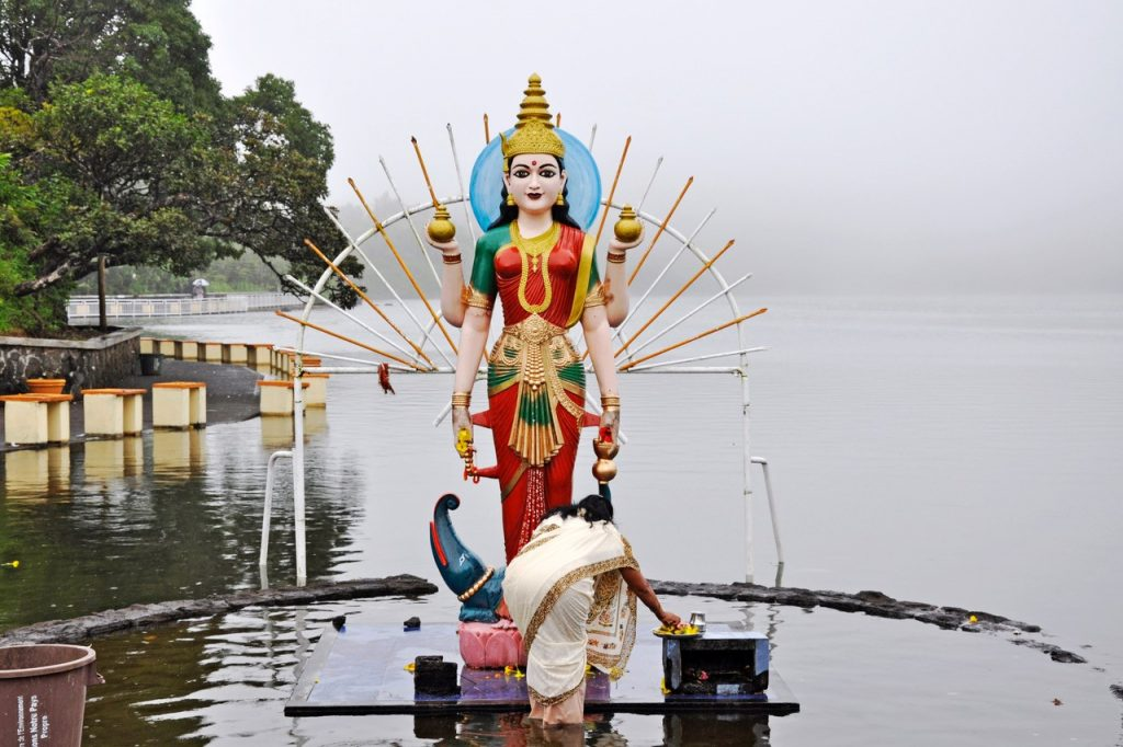 A woman performs a religious ritual in front of a Hindu statue in front of a lake.