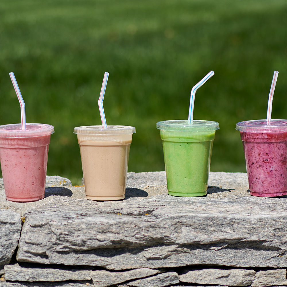 Four smoothies sitting on a rock wall.