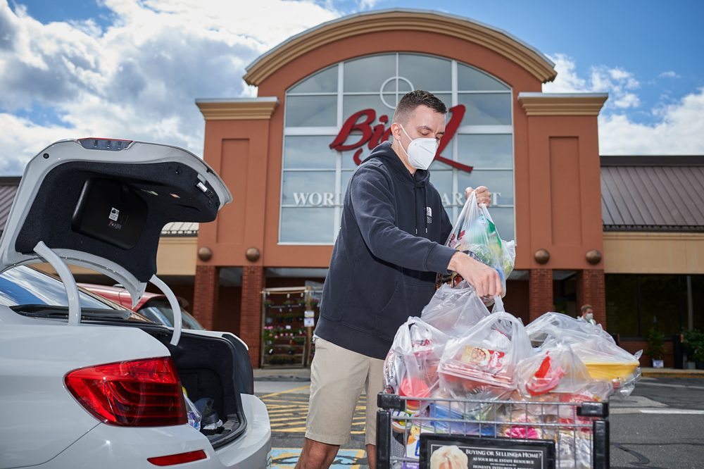 UConn alumn putting bags of groceries into car trunk.