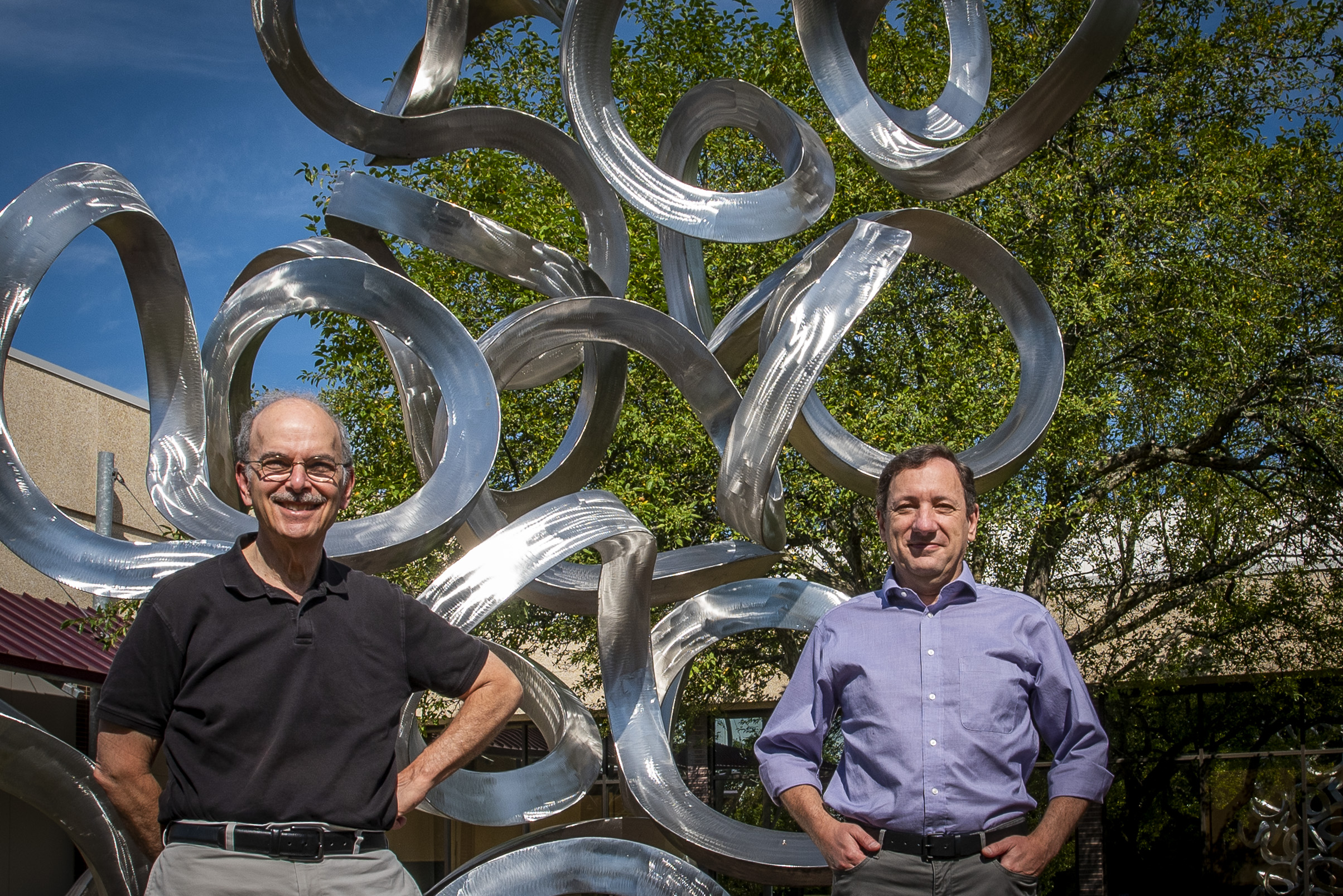 Researchers Les Loew, left, and Pedro Mendes outside the Cell and Genome building at UConn Health in Farmington on July 13, 2020.