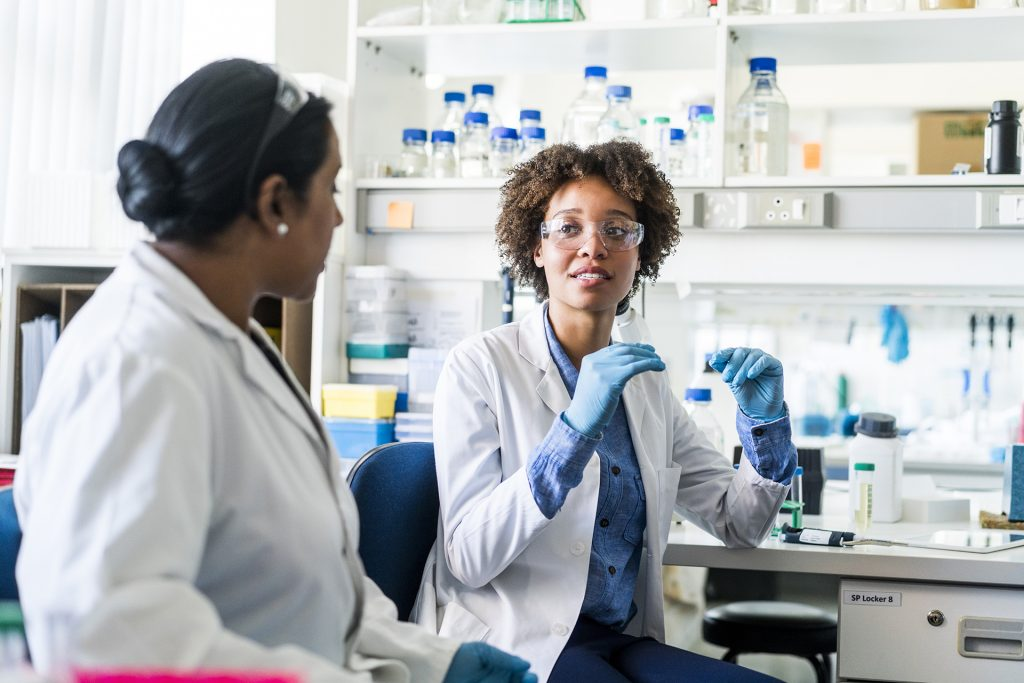 Young scientist discussing with colleague. Female researcher is sharing her ideas during meeting. They are wearing uniforms in laboratory.