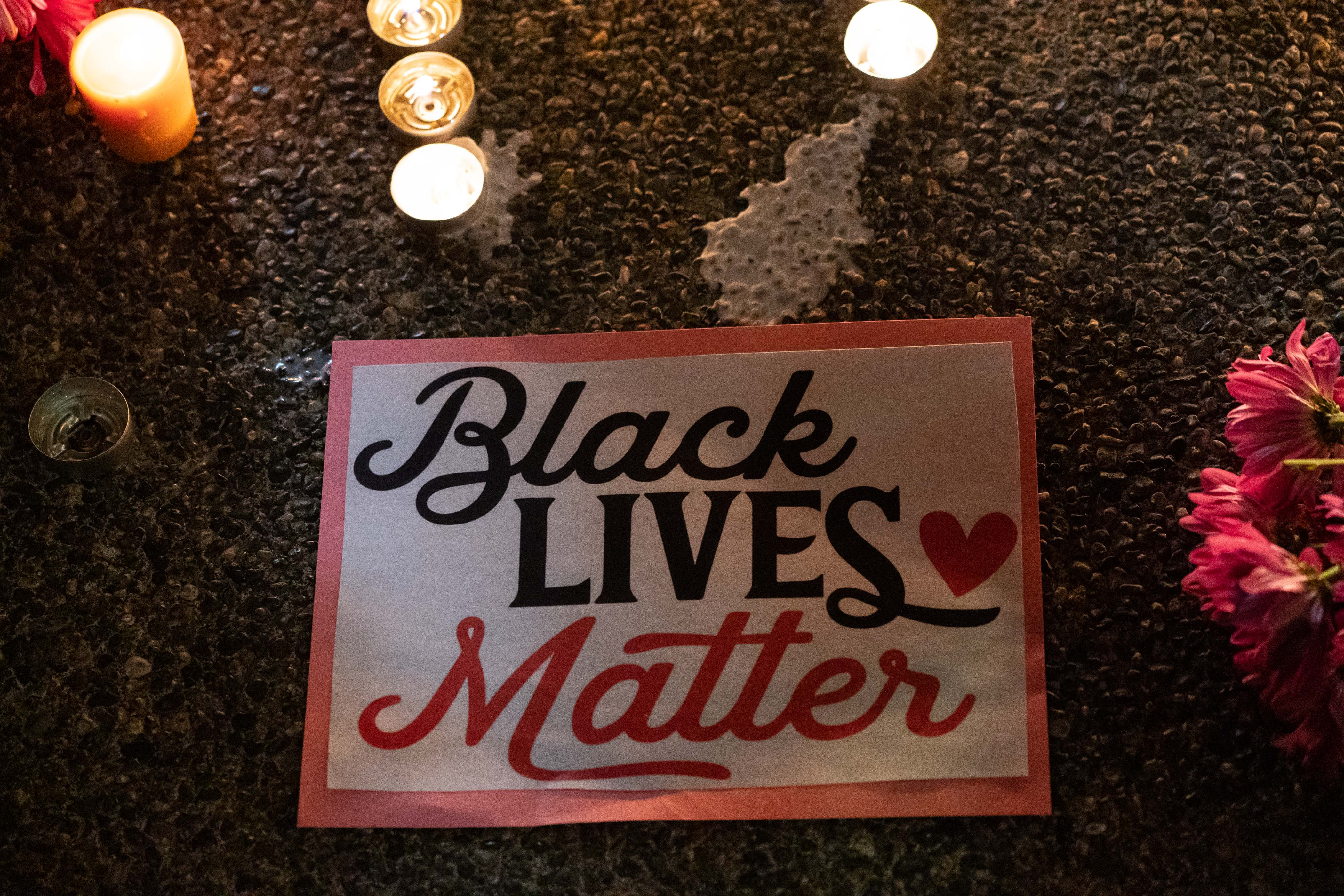 """A sign on the ground saying """"Black Lives Matter,"""" surrounded by flowers and candles."""