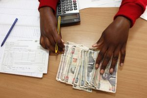 A woman counts non-American money on a table with a calculator and office paperwork