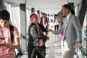 Neag School alum and school superintendent Nathan Quesnel greets a student at East Hartford High.