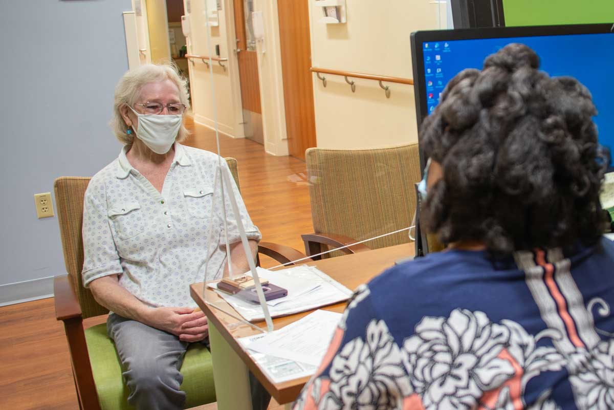 patient and scheduler in masks in the GI clinic