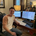 James Kolb smiles while working at his new at-home desk setup.
