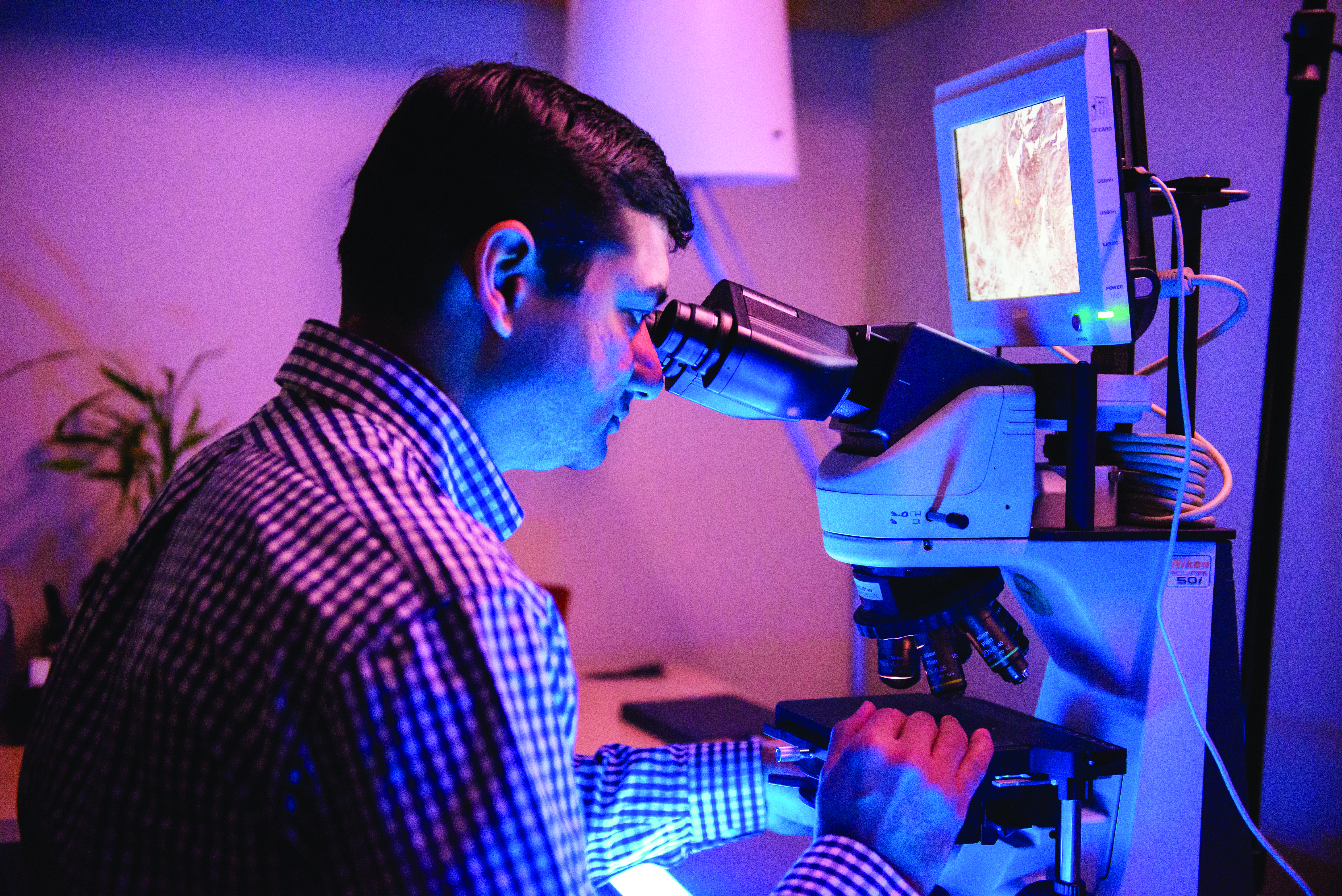 UConn School of Dental Medicine oral pathologist Easwar Natarajan, BDS, D.M.Sc., examines a sample under a microscope.