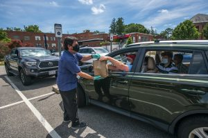 David Hille delivers ice cream to the Criss Family in the parking lot of the UConn Dairy Bar which opened to the public in limited compactly due to the covid 19 epidemic on June 24, 2020. (UConn photo/SeanFlynn)