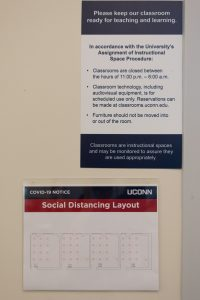 Two signs in a classroom with new social guidelines.