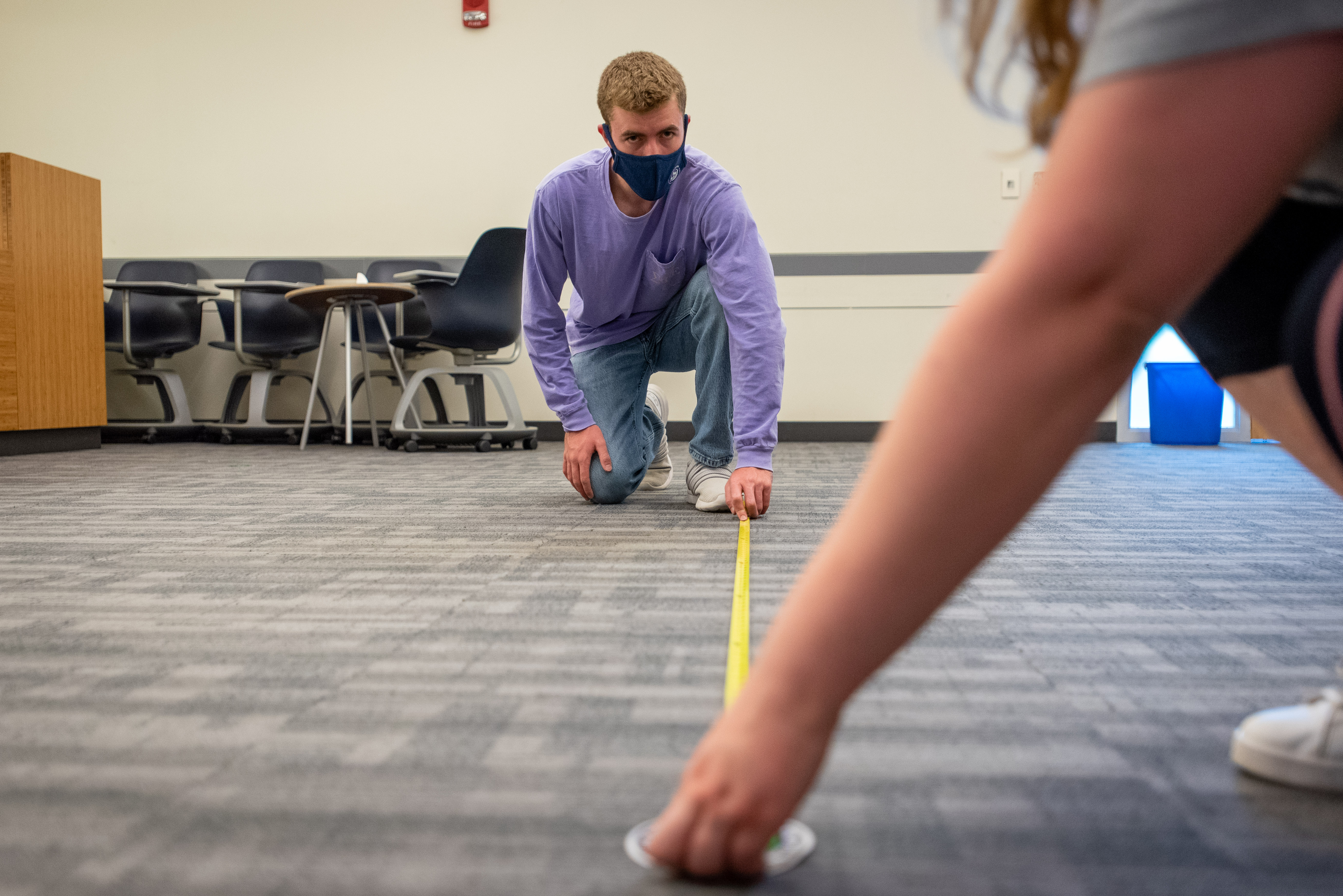 Two people in masks use a tape measure in a classroom to mark off space needed between desks.