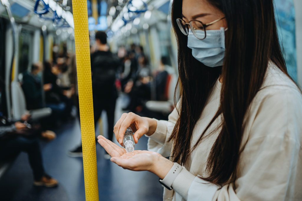 Young woman cleaning hands with alcoholic hand sanitizer to prevent the spread of viruses while commuting in the city riding on subway