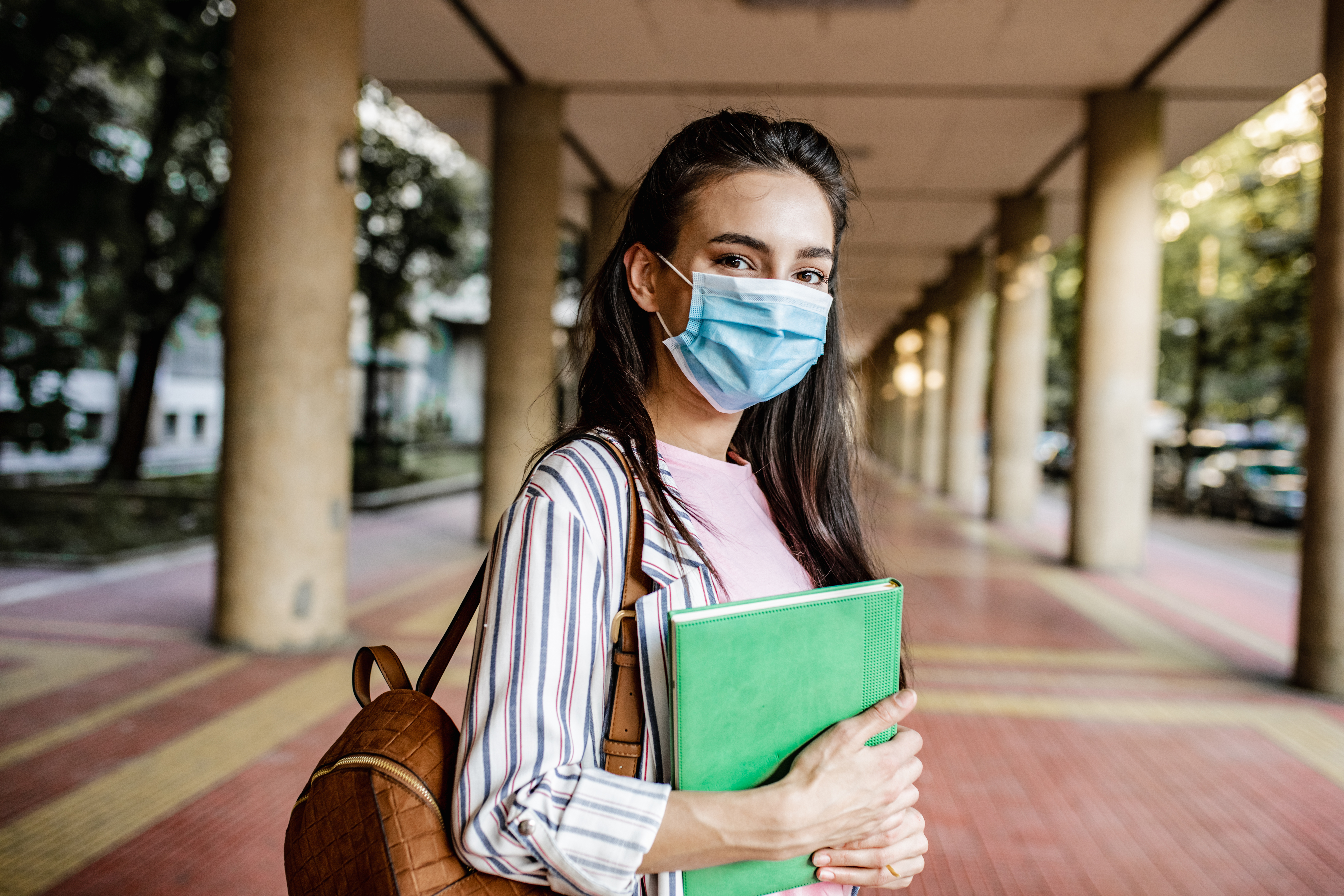 A young woman is holding a notebook and wearing a face mask