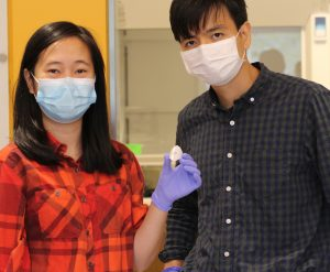 Professor Thanh Nguyen (right) with PhD student Khanh Tran, holding the microneedle patch they developed.
