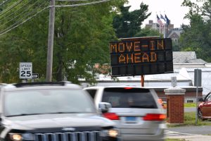 Cars along RT195 pass a sign announcing campus move in on Aug. 14, 2020. (Peter Morenus/UConn Photo)
