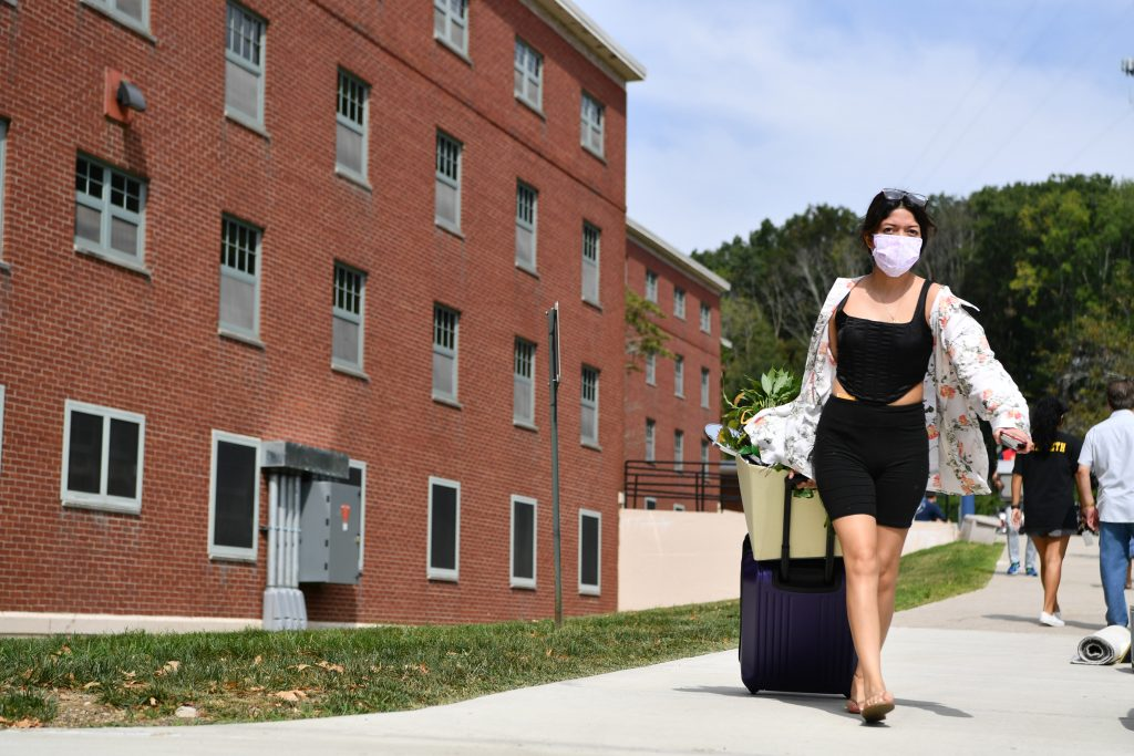 A student with a face covering moving into her dorm room at UConn