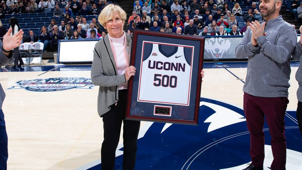 Field hockey coach Nancy Stevens holding a framed jersey with the number 500 on it, a gift she received after her 500th win as a UConn coach