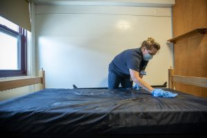 Custodian Shannon Miller sanitizes student's rooms in McMahon Residence Hall during the Covid 19 pandemic on July 2, 2020. (UConn photo/SeanFlynn)