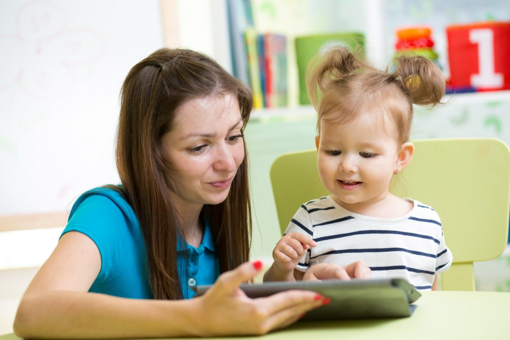 Parent holding tablet for child.