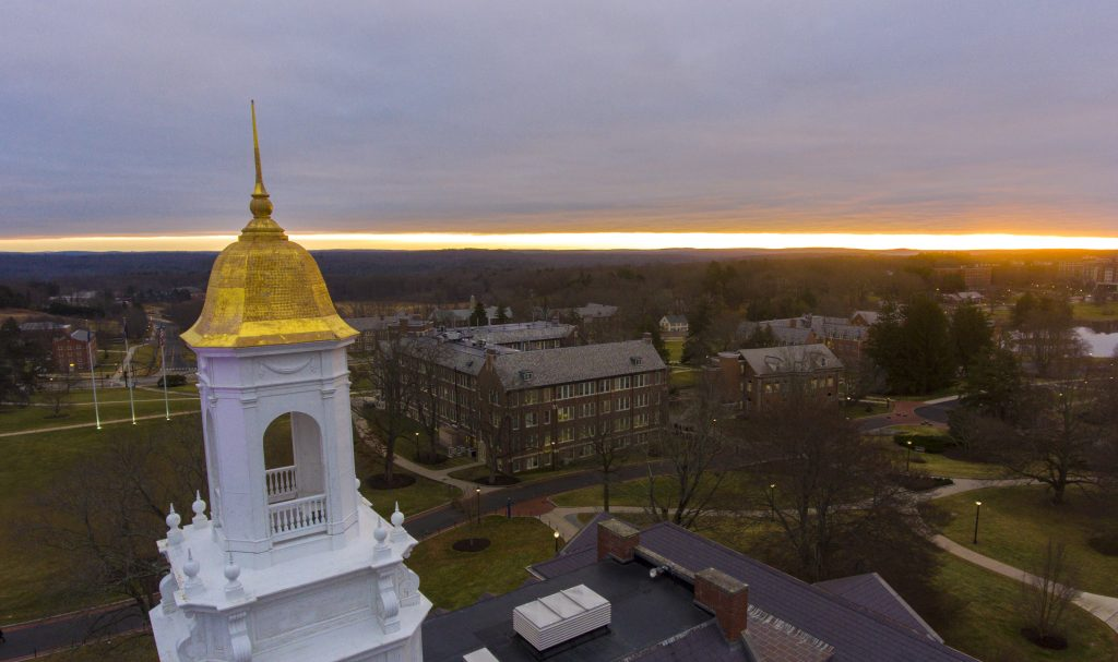 An aerial photo of the gold cupola of the Wilbur Cross building as the sun rises in the horizon