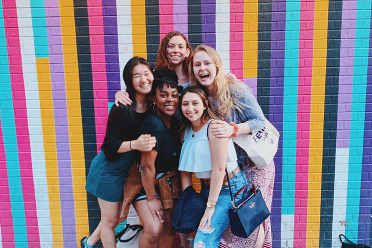 BOLD members in front of striped painted wall