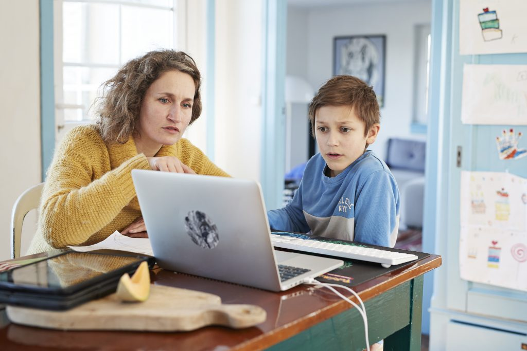 A mother helps her son with school work on a laptop computer.